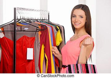 Woman shopping. Beautiful young woman choosing dress in retail store