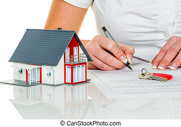 woman signs purchase agreement for house