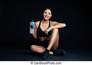 Woman sitting on the floor with bottle of water