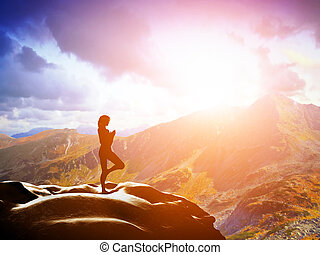 Woman standing in tree yoga position, meditating in mountains at sunset