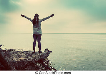 Woman standing on broken tree on wild beach with arms raised looking at sea