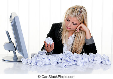 Attractive blonde woman sitting at a desk, surrounded by crumpled-up paper and looking for inspiration. Horizontal.