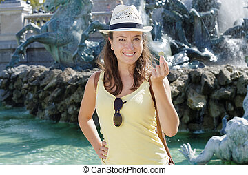 woman throws a coin in the fountain