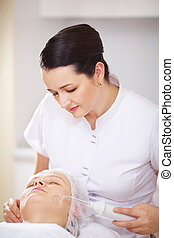 Woman under facial spa procedure