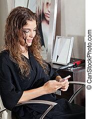 Woman Using Mobile Phone At Parlor