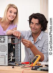 Woman watching her husband repair a computer