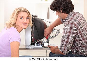 Woman watching husband fix television