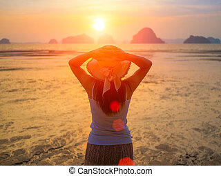 Woman wearing hat with open arms under the sunrise