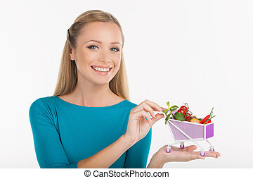 Woman with a miniature shopping cart. Cheerful young woman holding miniature shopping cart full of goods while isolated on white