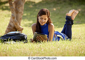 Woman with books and ipad studying for college test