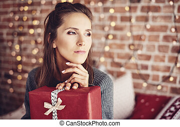 Woman with christmas present dreaming