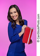Woman with gift box. Cheerful young woman holding a gift box and smiling at camera while isolated on colored background