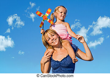 Woman with little girl against summer sky