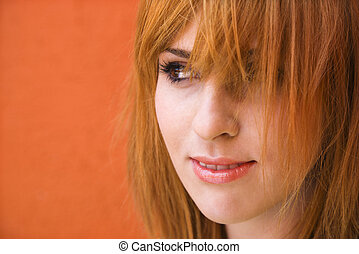 Close-up portrait of smiling young redheaded female looking mischievious.