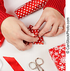 Woman wrapping present in a red paper