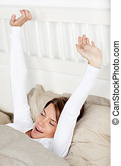 Woman yawning and stretching her arms