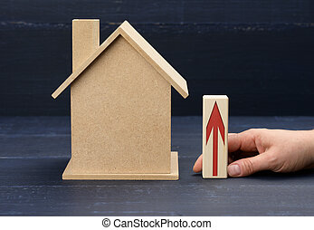 wooden house and a female hand holds a bar with a red arrow. Real estate value increase concept