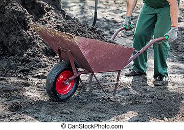 Worker transports a soil