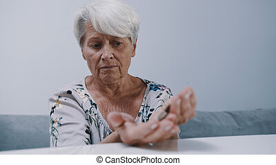 worried mature gray haired woman counting coins. Low pension concept