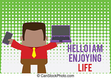 Writing note showing Hello I Am Enjoying Life. Business photo showcasing Happy relaxed lifestyle Enjoy simple things Professional man holding laptop in left mobile phone right.