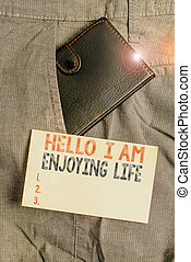 Writing note showing Hello I Am Enjoying Life. Business photo showcasing Happy relaxed lifestyle Enjoy simple things Small wallet inside trouser front pocket near notation paper.