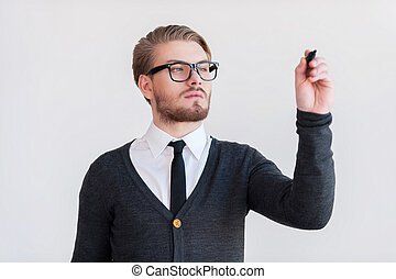 Writing on transparent wipe board. Handsome young man in glasses keeping arms crossed and while standing against grey background