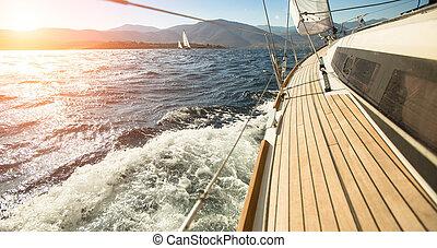 Yacht sailing towards the sunset. Sailing. Luxury yachts.