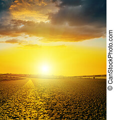 yellow sunset with dark clouds over asphalt road