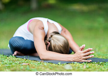 Girl doing Yoga, seated forward bend. Focus on hands, convenient copy space