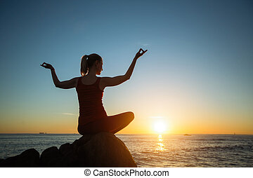 Yoga silhouette of young woman on the sea beach at amazing sunset.