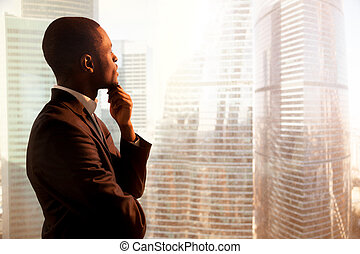 Young african-american thoughtful businessman looking through wi