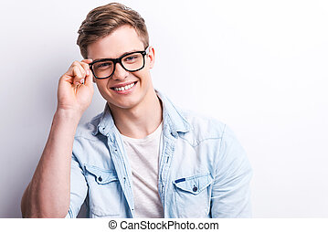 Young and creative. Handsome young man adjusting his eyewear and smiling while standing against grey background.