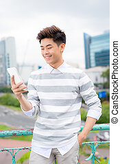 Young asian handsome businessman smiling while reading his smartphone. Portrait of asian business man reading message with smart phone in outdoor.