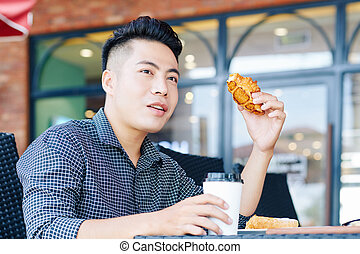 Young Asian man having cooffee and pastry