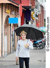 Young Asian Man Walking with Umbrella