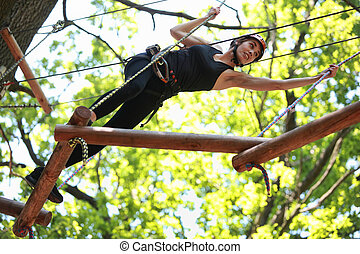 Young atractive woman climbing in adventure rope park in mountain helmet and safety equipment