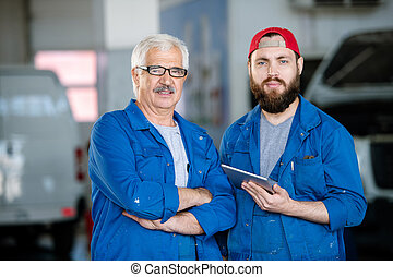 Young bearded technical service worker and his mature colleague in workwear