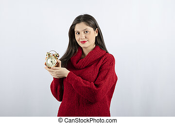Young beautiful brunette woman holding an alarm clock standing over