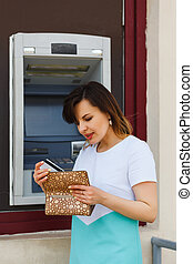 Young beautiful woman pulls out a bank card