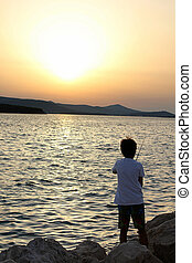 young boy fishing at sunset