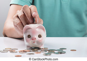 Young businessman depositing money in piggy bank