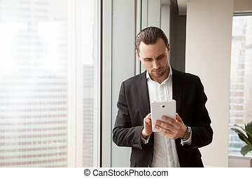 Young businessman in suit looking for information on electronic