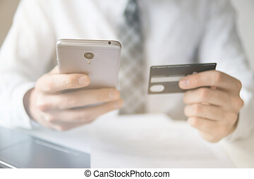 Young businessman with a bank credit card in his hands. Online trading on the currency exchange. Payment of goods online. Smartphone and Internet Commerce. Online payments through the phone.