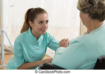 Young caregiver in nursing home