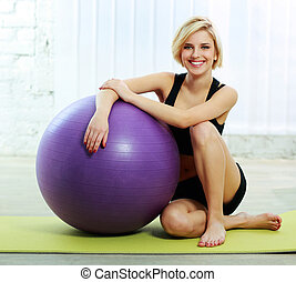 Young cheerful fit woman sitting on the floor with fitball