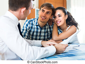 Young couple and banking agent indoors