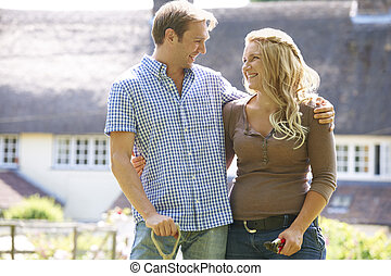 Young Couple At Home Working In Garden Together