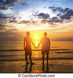 Young couple during honeymoon on a tropical beach, standing in the glow of an amazing sunset.