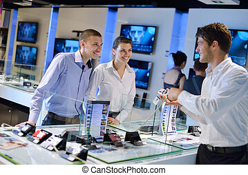 Young couple in consumer electronics store looking at latest laptop, television and photo camera to buy