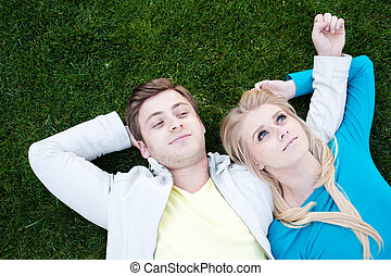 young couple in love lying in grass